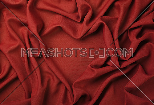 Close up abstract textile background of heart shaped red folded pleats of fabric, elevated top view, directly above