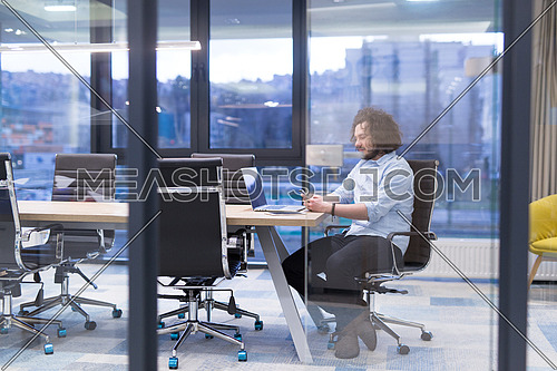 Young casual businessman using smartphone in the startup office