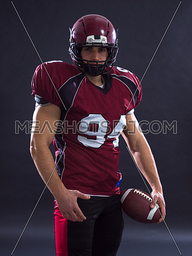 Portrait of a strong muscular American Football Player isolated on gray