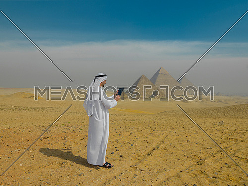 arab business man using tablet computer in desert with great giza pyramids in background