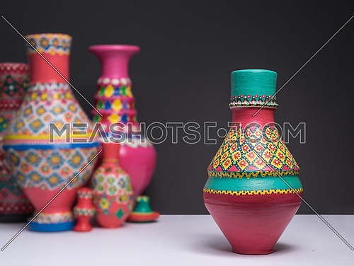 Decorated colorful pottery vase on background of blurred colorfu