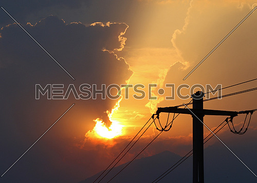 High voltage power lines in front of sun setting behind storm clouds