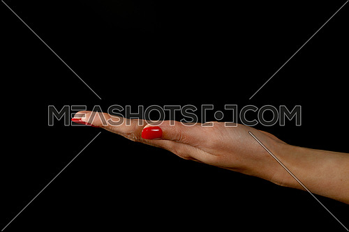 Woman hand palm with red nails holding or presenting something over black background, side view