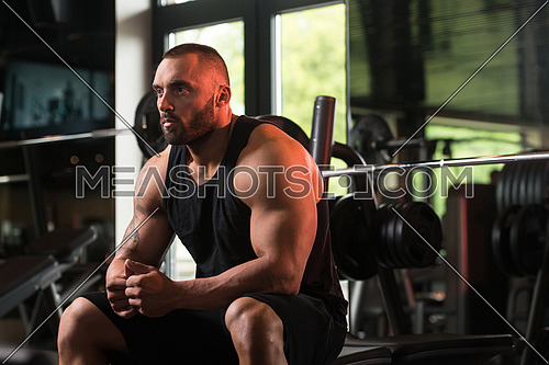 Big Bodybuilder Resting At The Bench In A Gym
