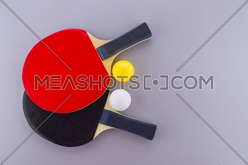 Red and black table tennis racks with a white and an yellow ping pong ball on grey background