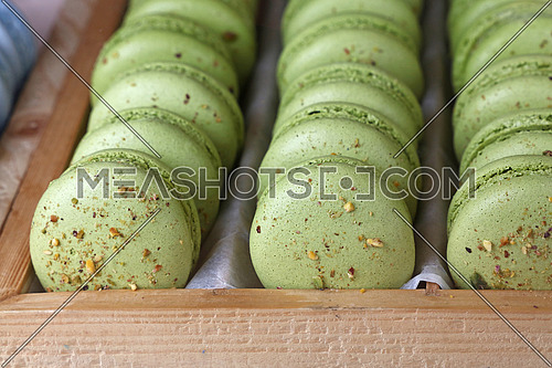 Fresh baked pistachio green macaroon pastry cookies (macarons, macaroni) in wooden box of retail store display, close up, high angle view