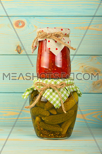 One glass jar of homemade eggplant pepper salad on jar of pickled cucumbers with green checkered textile decoration over blue painted wooden surface