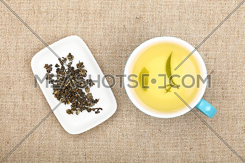 Big full cup of green tea and white plate with dried green tea leaves on flax canvas tablecloth, close up, elevated top view, directly above