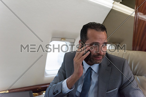 young middle eastern successful businessman talking on the phone while sitting in a private airplane