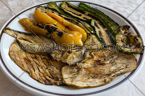 In the picture zucchini, peppers and eggplant grilled and served on white plate at restaurant.
