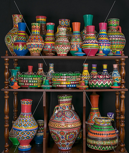 Group of colorful painted pottery crafts stacked in wooden storage shelves over black background