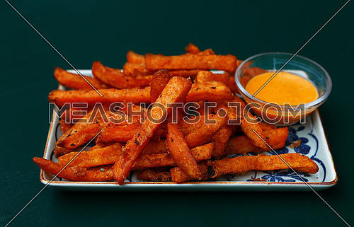 Portion of deep fried sweet potato chips or fries with dipping sauce on plate over table, high angle view
