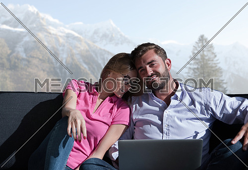 Young couple relaxing at  home using laptop computers reading in the living room near the window on the sofa couch.