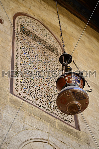 A ceiling lamp with islamic writings hanged in an old mosque with a decorated window on the background, in colors
