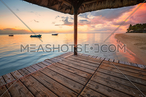 Perspective view of a wooden pier that create two amazing frame at sunset,tropical beach in Mauritus island