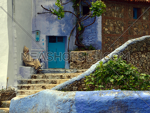 an old man sitting in-front of door entrance