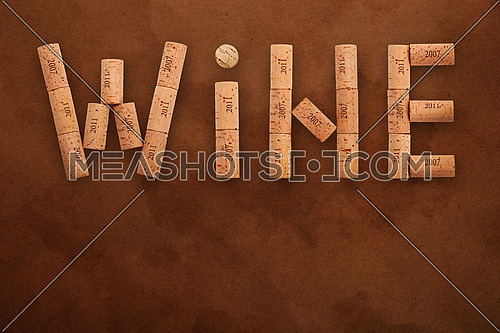 Word WINE shaped by natural wooden wine bottle corks of different vintage years over background of dark brown paper parchment