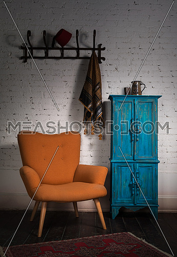 Composition of vintage orange armchair, blue cupboard, wall hanger with ornate scarf and red fez in studio