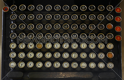 Latinic keyboard of old vintage antique typewriter with round buttons close up, high angle view, personal perspective