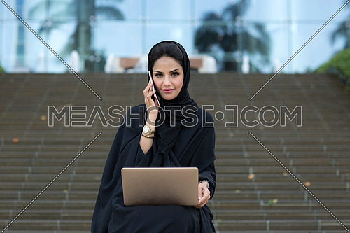 Mid-shot for Saudi lady setting down, holding laptop while making a call , wearing black abaya in front of glass building ladder in background at day.