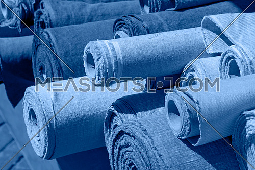 Close up assorted rolls of flax linen fabric and canvas textile on retail market stall, high angle view, blue toned