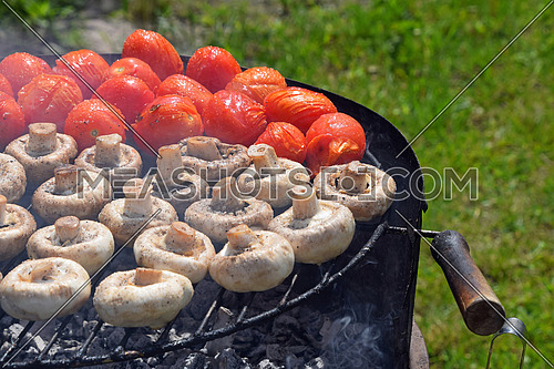 Vegetables in salt and spices being cooked outside on round summer grill, white champignons portobello mushrooms and red small tomatoes