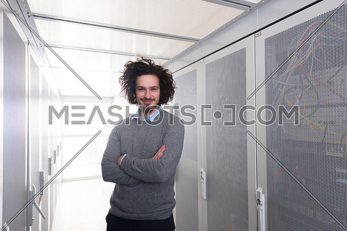 portrait of young handsome IT engeneer in datacenter server room