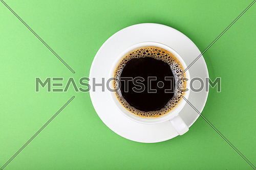 Close up one full white cup of black Americano coffee and saucer over pastel green paper background, elevated top view, directly above