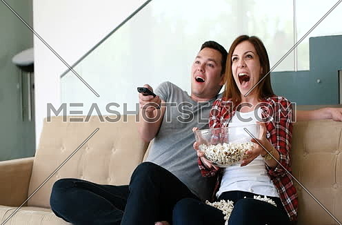 Couple Home Relaxing In Sofa And Watching Tv while eating popcorns