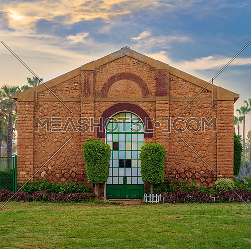 Side view of the Royal Plant Nursery with closed grunge door and orange painted bricks stone wall decorated with plants in sunrise time at Montaza public park, Alexandria, Egypt