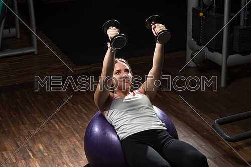 Young Woman Doing Heavy Weight Exercise For Chest