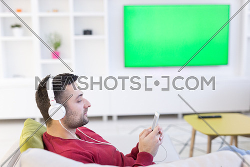 Young handsome man enjoying music through headphones, laying on sofa at home