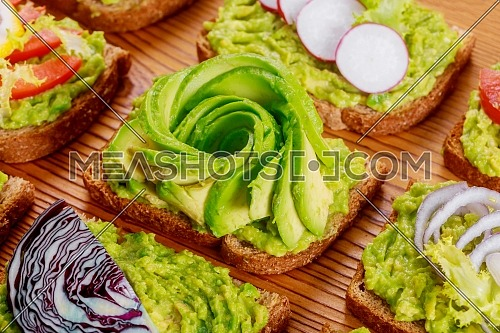 Wholegrain toasted bread with homemade toast sandwich with avocado and jam on wooden board healthy food