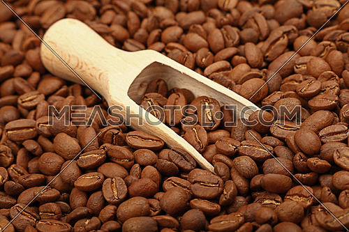 Close up wooden scoop with roasted coffee beans, high angle view