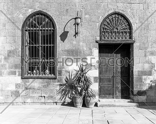 Black and white shot of fold abandoned stone bricks wall with arched wooden door and window covered with wrought iron bars and lantern, Cairo, Egypt