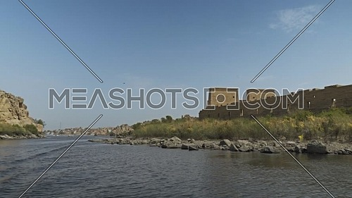 reveal shot for Temple of Philae li from the boat in the River Nile at Aswan - Egypt by day