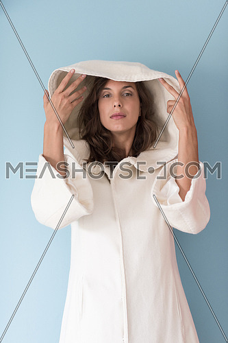 portrait of Beautiful young woman wearing a white coat with hood isolated on blue background