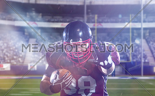 American football player holding ball while running on field of big modern american football stadium with lights and flares at night
