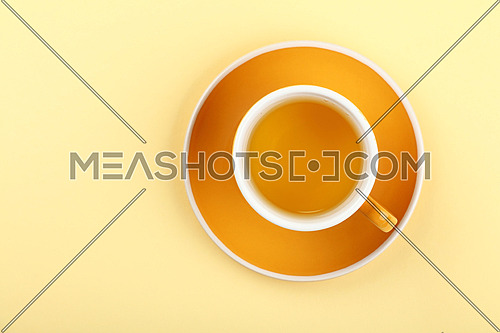 Close up one full yellow cup of green oolong or herbal tea on saucer over pastel paper background, elevated top view, directly above