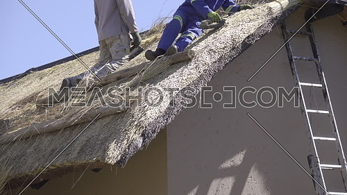 Scene of two African construction workers on roof