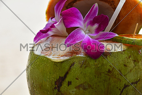 Fresh open green coconut milk juice with straw decorated garnished with tropical purple orchid flowers and orange slice at sand beach background