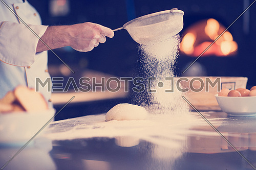 chef sprinkling flour over fresh pizza dough on kitchen table