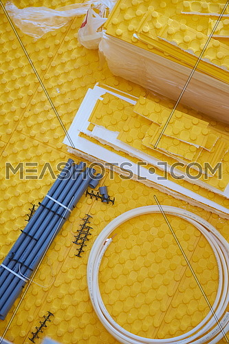yellow underfloor heating posed in a under construction building
