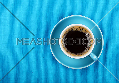 Full cup of black Americano or instant coffee on saucer over blue tablecloth, close up, elevated top view