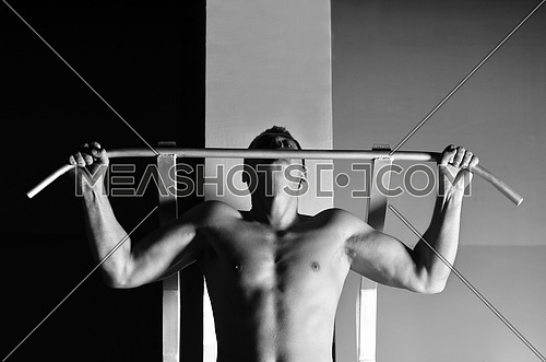 young man with strong arms working out in gym and representing their streinght and vitality