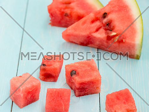 Pieces of watermelon on blue wooden background