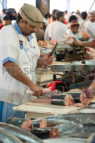 sales man cutting fish in Fish Market In Dubai
