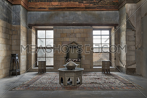 Hall at the palace of Prince Taz with stone bricks wall decorated by calligraphy with two windows, historic chair and tables, Old Cairo, Egypt