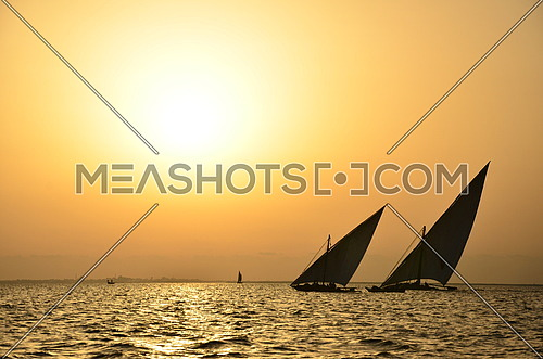 two sail boats in the sea at sunset