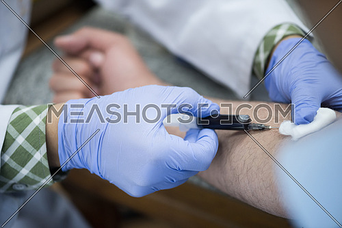 Young middle eastern Medical technologist doing a blood draw services for patient.